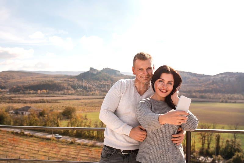 Pares felizes que fazem o selfie contra as montanhas imagem de stock