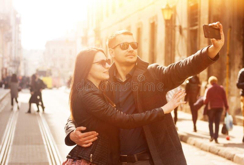 Pares felizes que fazem o selfie na rua Imagem ensolarada tonificada fotografia de stock