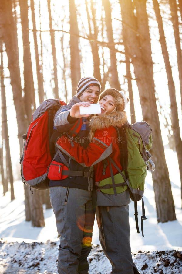 Pares felizes que fazem o selfie no inverno imagens de stock royalty free