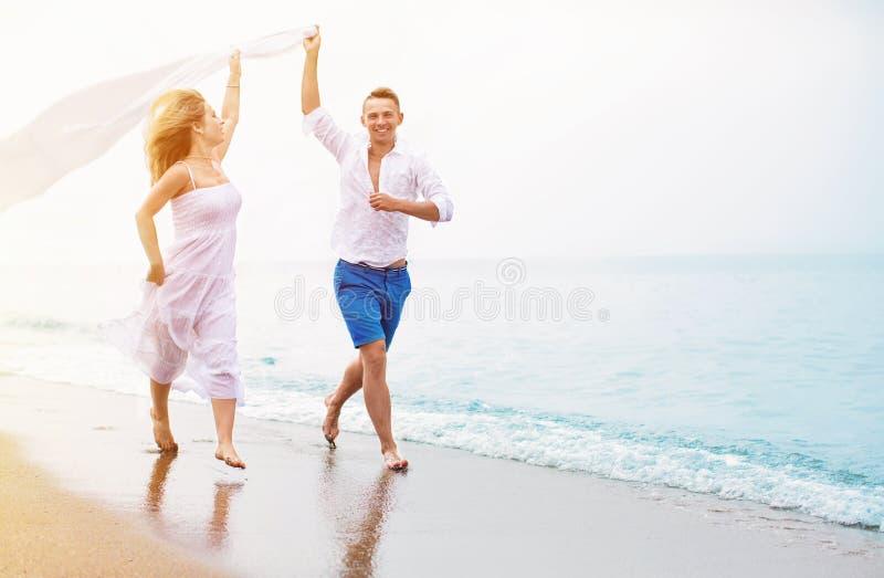 Pares felizes que funcionam na praia fotografia de stock