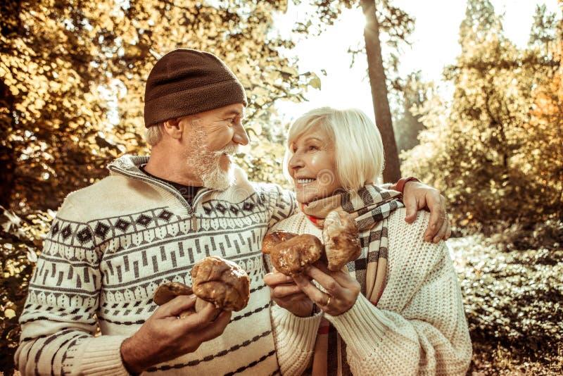 Pares felizes que guardam cogumelos grandes e aperto imagens de stock royalty free