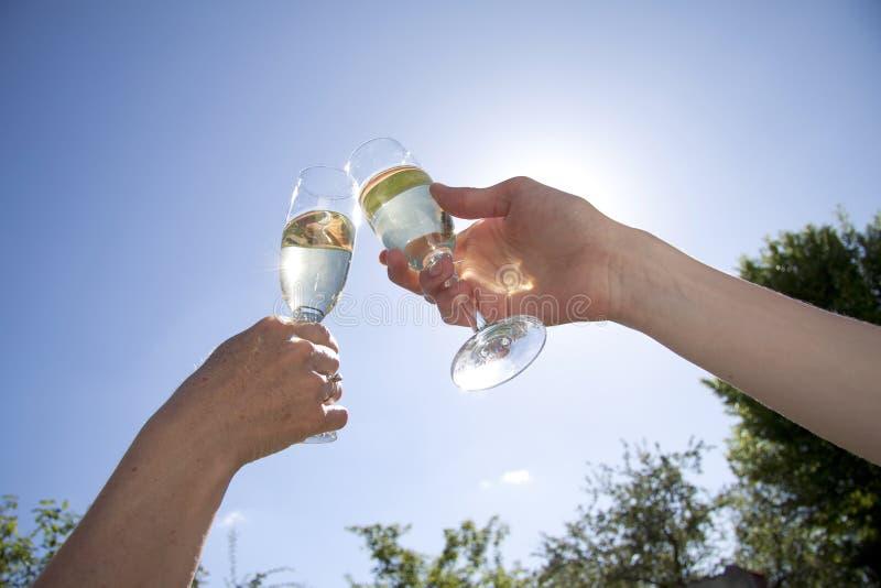 Pares felizes que guardam vidros do champanhe e que aumentam os contra um céu azul claro do verão fotografia de stock