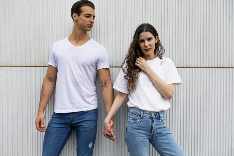 Pares felizes que inclinam-se contra a parede que guarda as mãos que vestem a roupa ocasional em um dia brilhante foto de stock