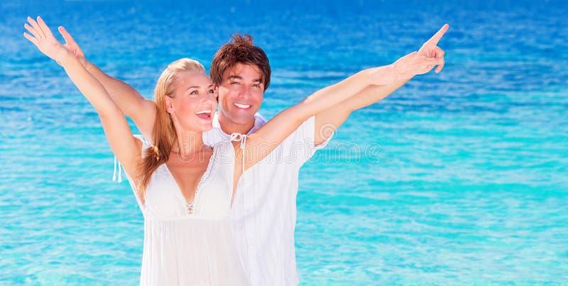 Pares felizes que jogam na praia fotografia de stock royalty free