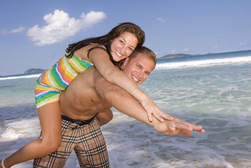 Pares felizes que jogam na praia imagem de stock royalty free