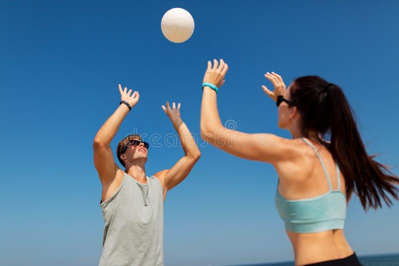 Pares felizes que jogam o voleibol na praia do verão imagem de stock royalty free