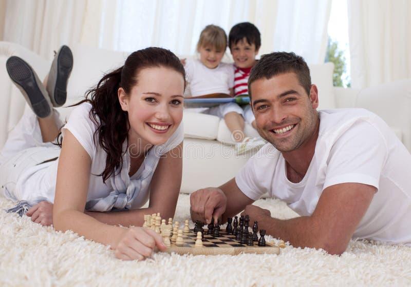 Pares felizes que jogam a xadrez no assoalho na sala de visitas fotos de stock royalty free