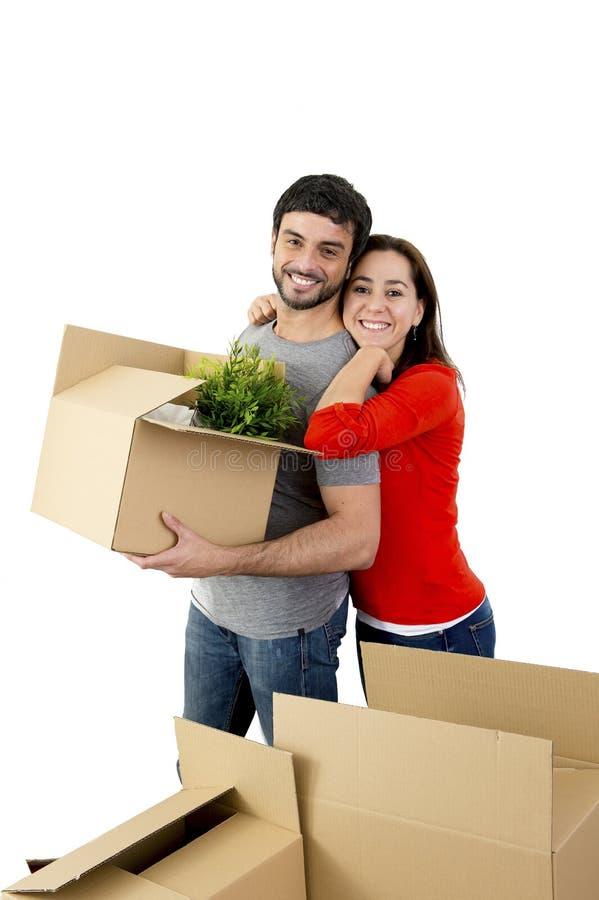 Pares felizes que juntam em uma casa nova que desembala caixas de cartão imagens de stock royalty free