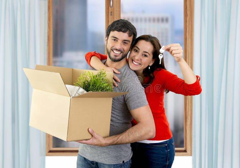 Pares felizes que juntam em uma casa nova que desembala caixas de cartão imagens de stock