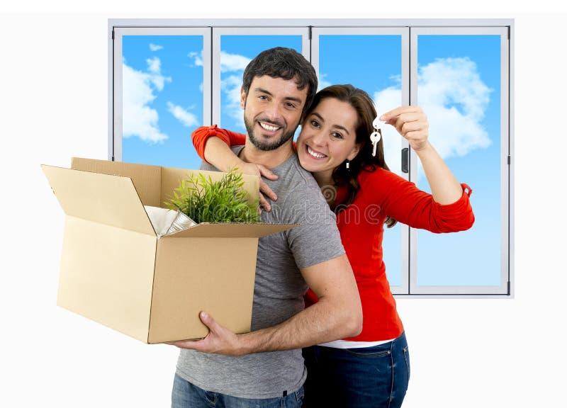 Pares felizes que juntam em uma casa nova que desembala o cartão fotografia de stock