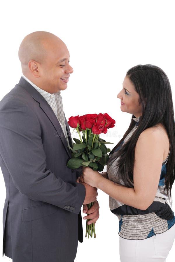 Pares felizes que mantêm um ramalhete de rosas vermelhas isolado fotografia de stock