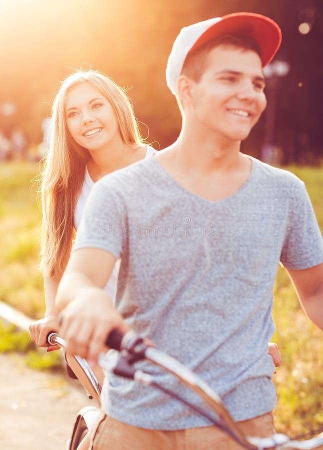 Pares felizes que montam uma bicicleta na rua da cidade fotos de stock