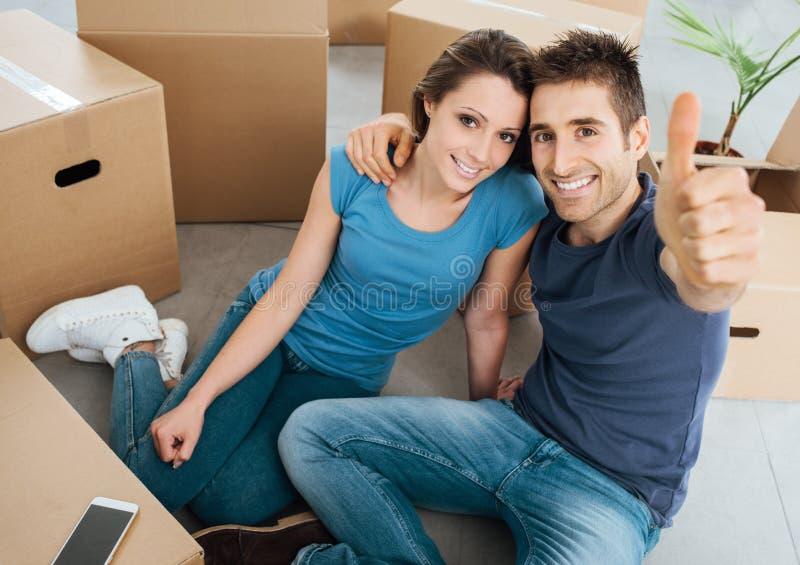 Pares felizes que movem-se em sua casa nova fotos de stock