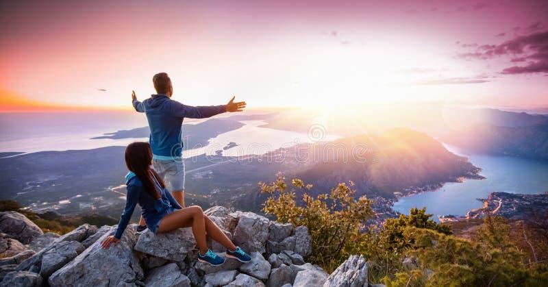 Pares felizes que olham o por do sol nas montanhas fotos de stock royalty free