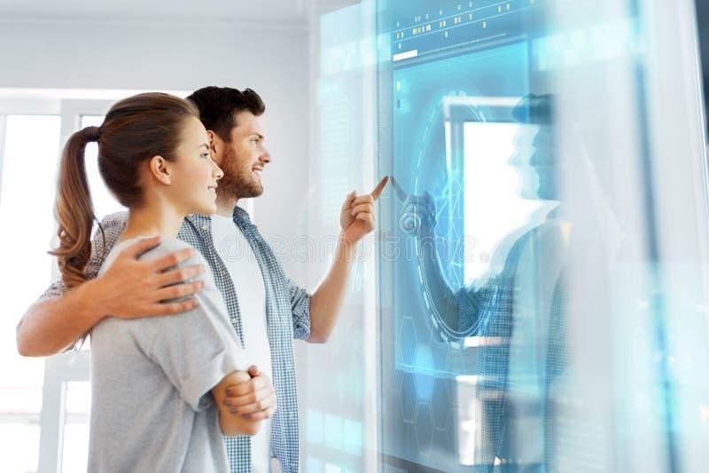 Pares felizes que olham a tela virtual futurista fotografia de stock