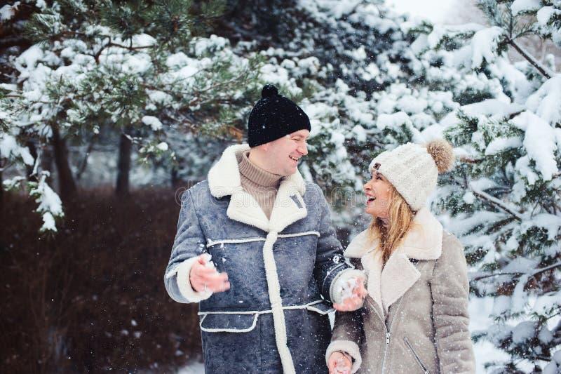 Pares felizes que passam o bom dia exterior no inverno nevado imagem de stock royalty free