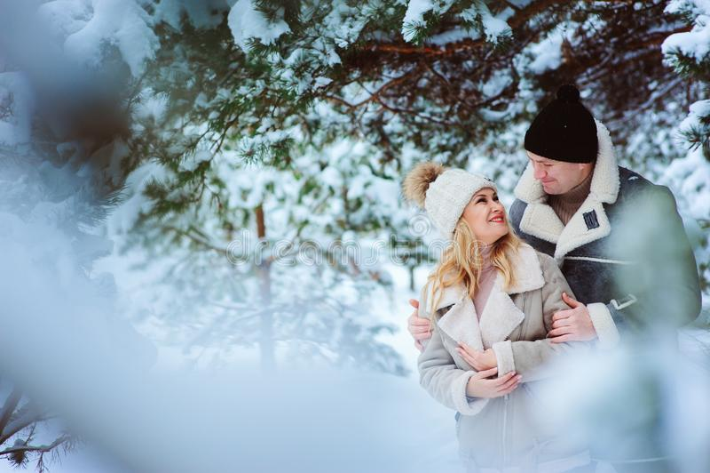 Pares felizes que passam o bom dia exterior no inverno nevado fotos de stock royalty free