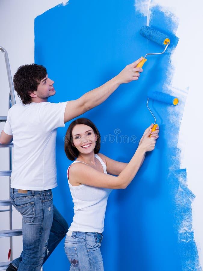 Pares felizes que pintam a parede foto de stock