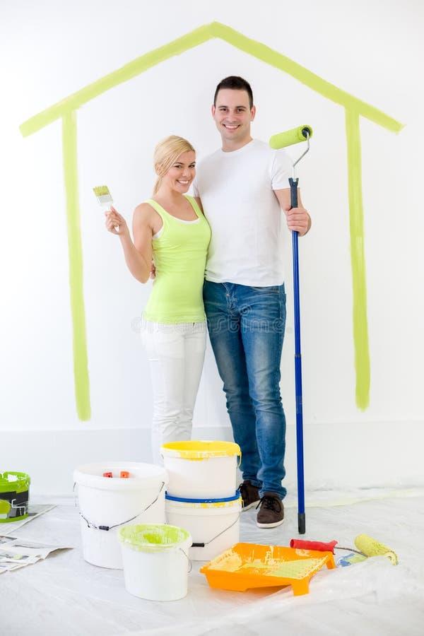 Pares felizes que pintam sua casa nova imagem de stock