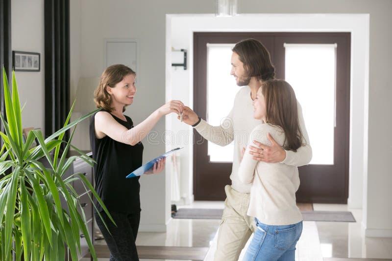 Pares felizes que recebem chaves da casa do corretor de imóveis imagem de stock royalty free