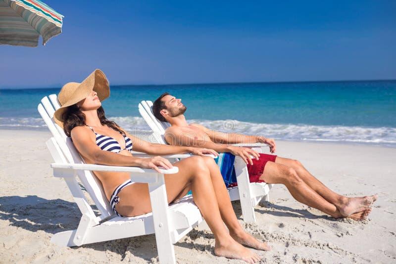 Pares felizes que relaxam na cadeira de plataforma na praia imagem de stock