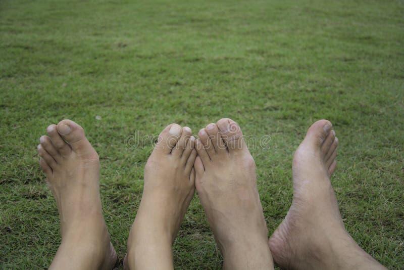 Pares felizes que relaxam na grama verde Pares que encontram-se na grama ao ar livre barefoot Homem e fêmea asiáticos foto de stock