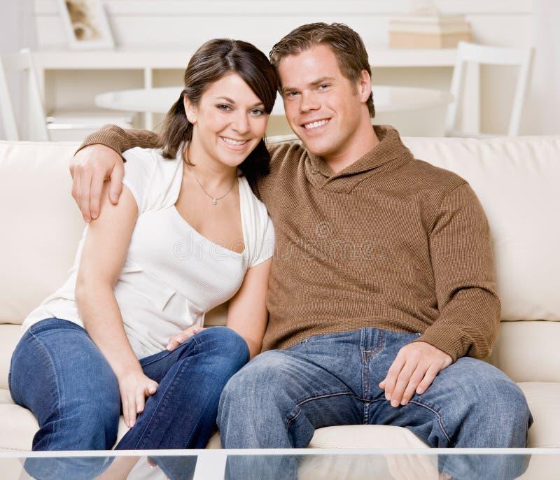 Pares felizes que relaxam no sofá fotos de stock