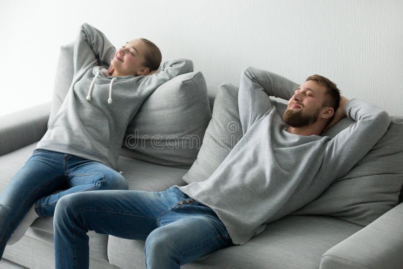 Pares felizes que relaxam tomando a sesta no sofá acolhedor em casa fotografia de stock royalty free