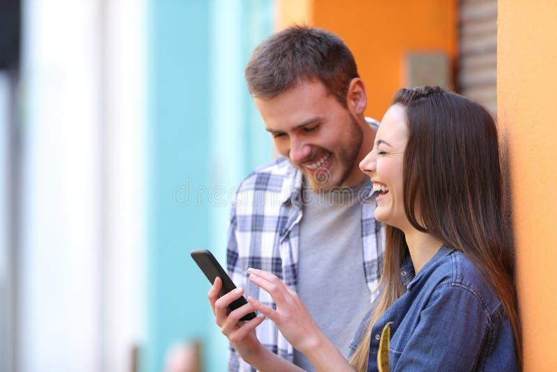 Pares felizes que riem verificando o telefone esperto imagens de stock royalty free