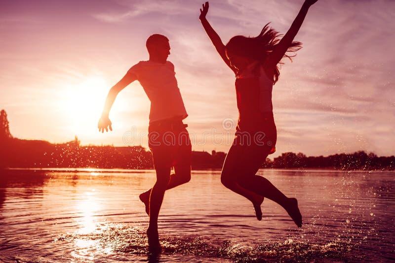 Pares felizes que saltam no banco de rio do verão Homem novo e mulher que têm o divertimento no por do sol Indivíduos que pendura fotografia de stock