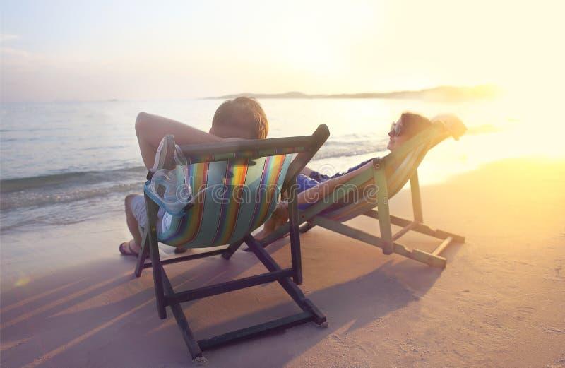 Pares felizes que sentam-se em cadeiras do sol na praia de Koh Samet em fotos de stock
