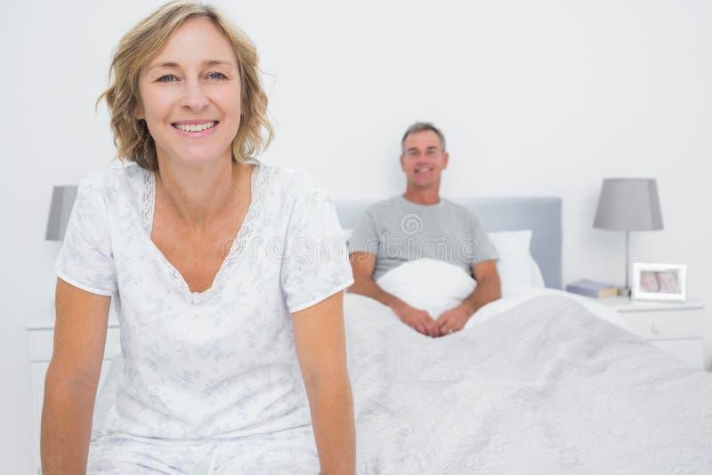 Pares felizes que sentam-se em extremos opostos da cama fotos de stock