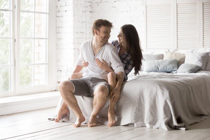 Pares felizes que sentam-se na cama que abraça a vista nos olhos foto de stock royalty free