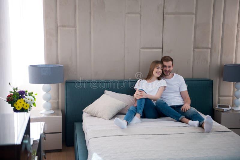 Pares felizes que sentam-se na cama com os descansos no quarto imagens de stock royalty free
