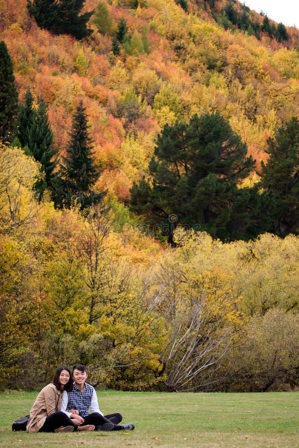Pares felizes que sentam-se na grama contra as árvores do fundo do outono fotos de stock royalty free