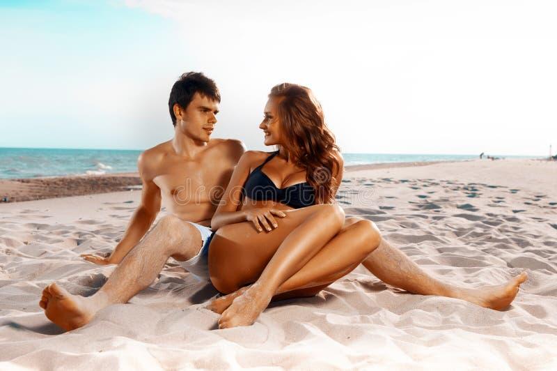 Pares felizes que sentam-se na praia fotografia de stock