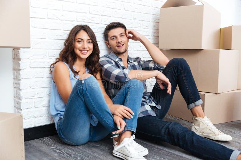 Pares felizes que sentam-se no assoalho em torno das caixas após ter comprado a casa imagens de stock royalty free