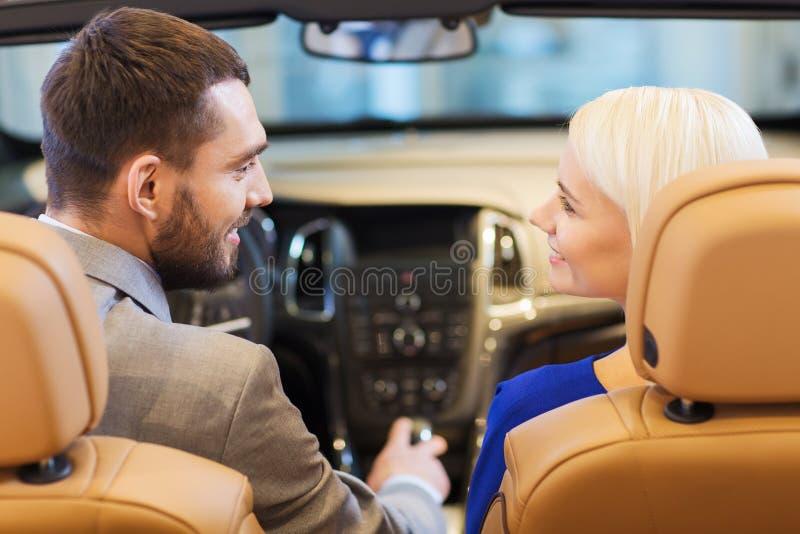 Pares felizes que sentam-se no carro na feira automóvel ou no salão de beleza imagens de stock