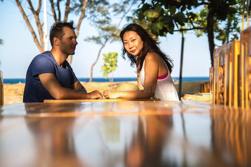 Pares felizes que sentam-se no ouside da tabela da barra em Tailândia foto de stock royalty free