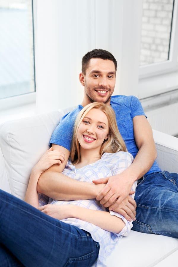 Pares felizes que sentam-se no sofá e que abraçam em casa fotos de stock