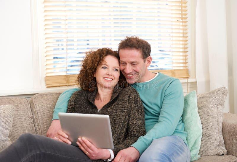 Pares felizes que sentam-se no sofá que olha a tabuleta do computador fotografia de stock