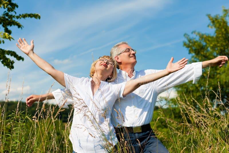 Pares felizes que têm o divertimento ao ar livre no verão foto de stock