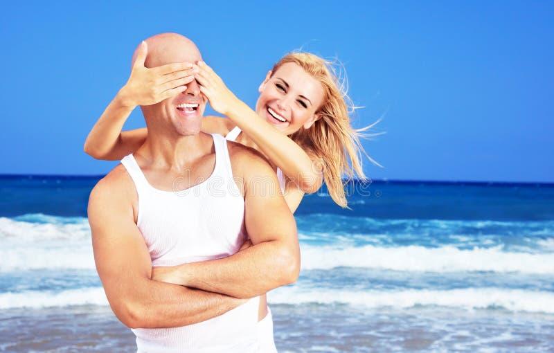 Pares felizes que têm o divertimento na praia imagens de stock