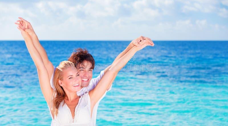 Pares felizes que têm o divertimento na praia fotografia de stock royalty free
