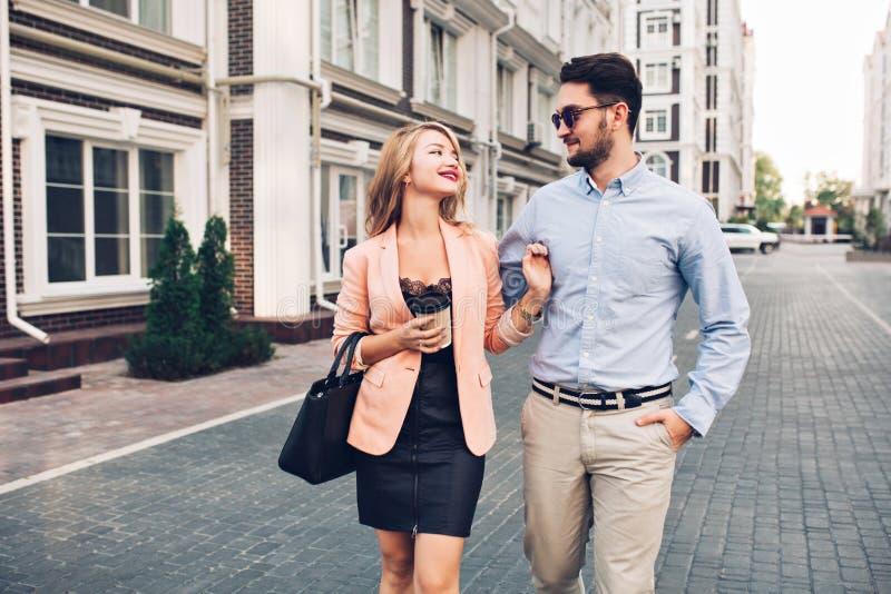 Pares felizes que têm o divertimento na rua na cidade O indivíduo farpado considerável nos óculos de sol está abraçando a menina  fotografia de stock royalty free