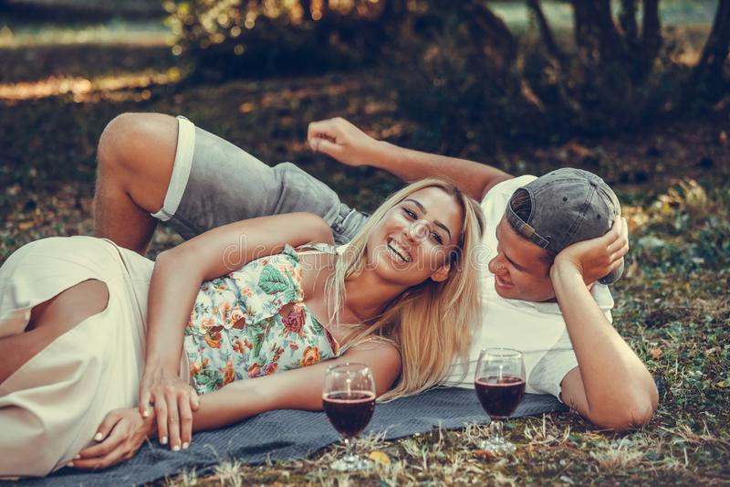 Pares felizes que têm um piquenique e que abraçam no parque fotografia de stock royalty free