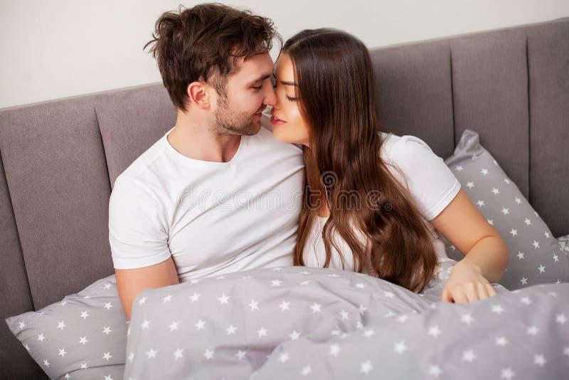 Pares felizes que t?m o divertimento na cama Pares novos sensuais ?ntimos no quarto que aprecia-se fotografia de stock