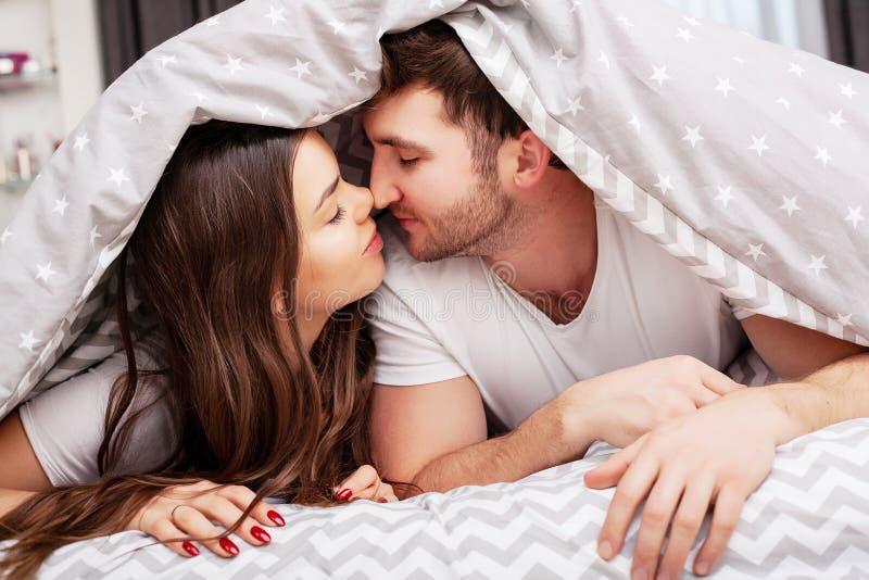 Pares felizes que t?m o divertimento na cama Pares novos sensuais ?ntimos no quarto que aprecia-se foto de stock royalty free
