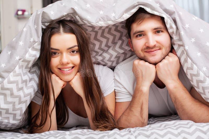 Pares felizes que t?m o divertimento na cama Pares novos sensuais ?ntimos no quarto que aprecia-se fotos de stock