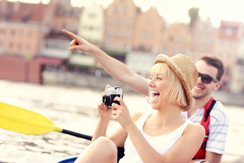 Pares felizes que tomam imagens em uma canoa imagens de stock